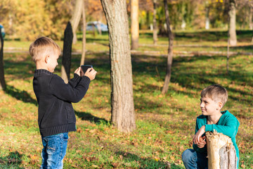 A boy takes pictures on his brother's smartphone in the park on a sunny day.