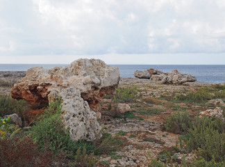 Rough coastal terrain with scattered large boulders on rocky cliff tops typical of menorca spain