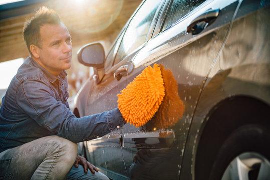 Men washing his car with wash mitt