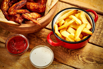 top view of delicious fried chicken wings and french fries on old wooden table