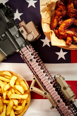 top view of delicious fried chicken wings, french fries and rifle against USA flag background