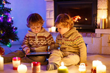 Two little children sitting by a fireplace at home on Christmas time. Happy cute adorable toddler boys, blond twins playing with new tablet gift. Family celebrating xmas holiday.