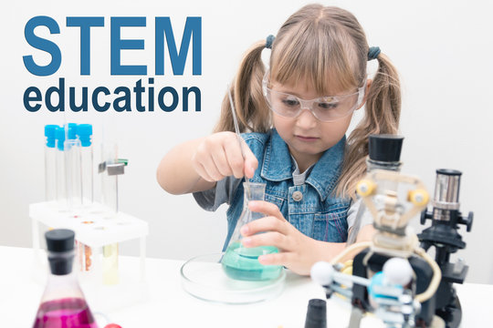 A girl child collect molecules and conduct chemical experiments. On the table is a robot. STEM education. Science and technology. Science school, Workshop.