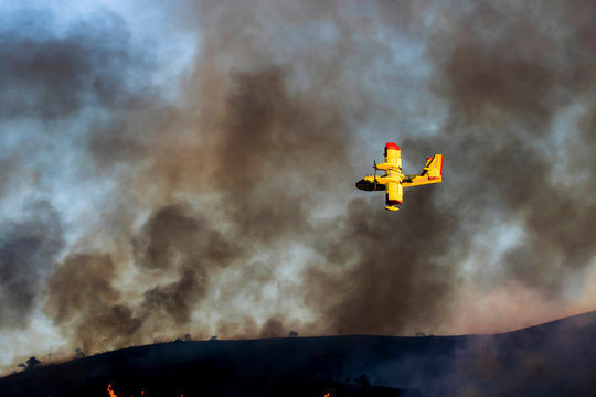 Yellow Plane Flies Over Brushfire with Smoke in Sky during California Woolsey Fire