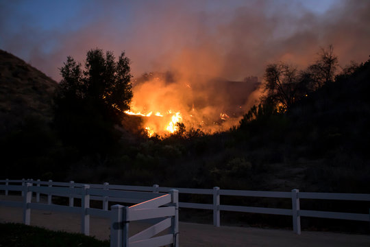 Fire Burning Hill Just Beyond White Park Fence in California Woolsey Brushfire