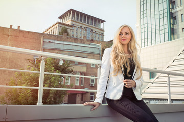 Young stylish blonde girl in a white jacket posing on street at the sunny day