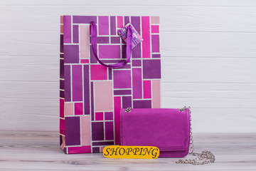 Printed shopping bag on wooden background. Feminine leather chain bag. Pink gift bag and yellow card with inscription shopping.