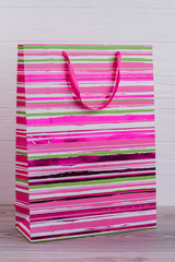 Vibrant paper shopping bag with handles. Laminated paper gift bag on wooden background, vertical image.