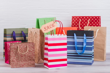 Multicolored paper shopping bags. Assortment of paper printed gift bags and card with inscription sale, horizontal image.
