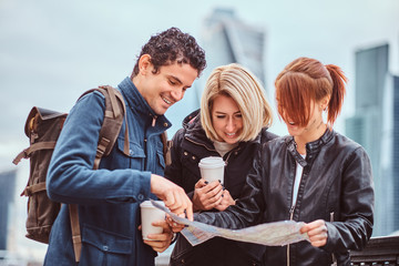 Group of happy tourists searching place on the map in front of skyscrapers