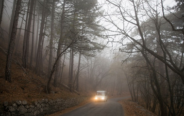 A minibus drives through the fog, along the road on Ai-Petri mountain outside Yalta