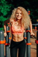 Photo curly blonde sports pulls up on sports simulator in park