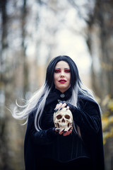 Photo of witch woman with skull in hands