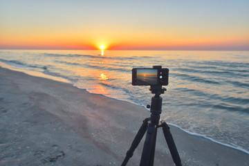 Sunrise over the sea coast. Fireball of the sun above the horizon in a colorful orange sky. Smartphone camera on a tripod in the foreground