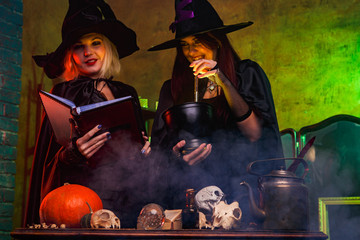 Image of smiling two witches in black hats reading book at table with pumpkin and skulls