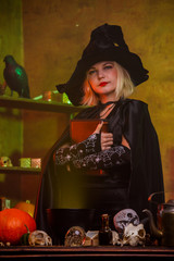 Photo of witch in black hat with spell book at table with pot, pumpkin