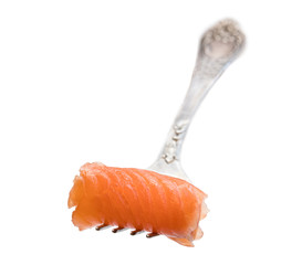 Rolled salmon piece on fork isolated on white