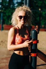Photo of sports woman wearing sunglasses holding phone in hands