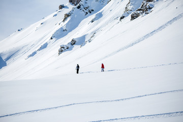 Photo from afar of two sporty skiers in snowy resort