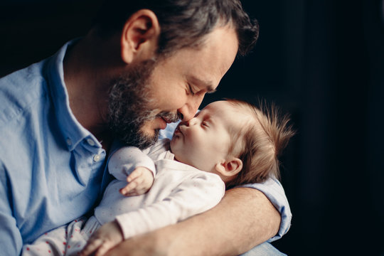 Closeup portrait of middle age bearded Caucasian father hugging and kissing newborn baby. Male man parent holding child. Authentic lifestyle touching tender moment. Single dad family life concept.