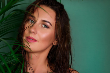 Young girl with wet hair, natural make up between tropical palm leaves on green background. Banner, copy space. Skin care, pure beauty, body treatment, fashion, cosmetics concept. Wall mural