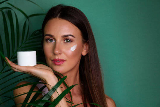 Beautiful young woman putting cream on pure skin between palm leaves on green background. Facial treatment, cosmetology, beauty and spa concept. Natural make up