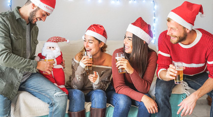 Happy friends having fun during christmas time sitting on sofa at home - Young people drinking beer together and enjoying xmas holidays - Youth celebration x-mas concept