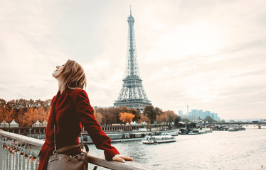 Style redhead girl in red coat and bag at parisian street with view at Eiffel tower in autumn season time Wall mural