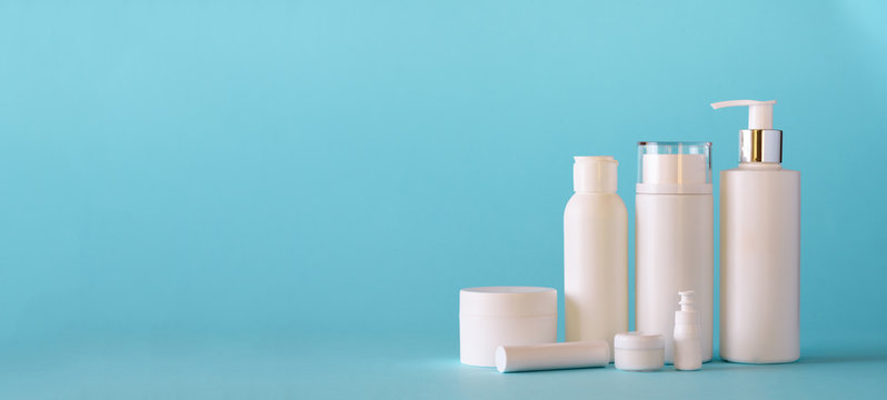 White cosmetic tubes on blue background with copy space. Skin care, body treatment, beauty concept. Banner