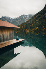 Girl sitting at cabin on the edge of lake