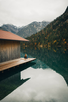 Woman sitting on deck by lake in autumn