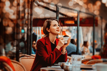 Style redhead girl in red coat with cup of coffee in parisian cafe. Autumn season time Wall mural