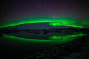 A beautiful green aurora borealis is dancing over the Jokulsarlon lagoon, in the foreground is its reflection on the lake´s surface. In the background are the northern lights above the mountains