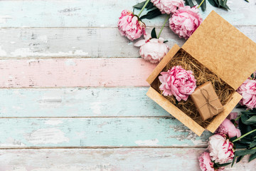 peonies and gift box on wooden table