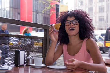Pretty young woman with afro hairstyle sitting outdoors drinking a cup of coffee and eating coxinha food. Brazilian snack in Sao Paulo during summer, busy street.
