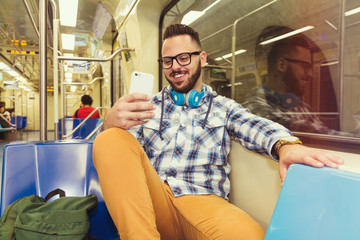 Traveler wearing glasses reading fun feeds on cell phone on subway metro . Concept of commute, connection, communication, social media.
