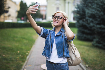 Young attractive woman is making selfie wearing glasses and backpack on the phone outdoors
