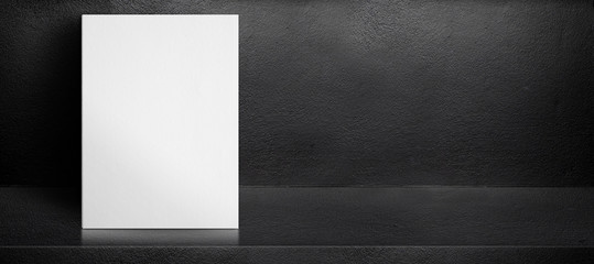 Blank white poster leaning at black interior cement room background,mock up banner template for display of design,leave side space for adding text for advertising.