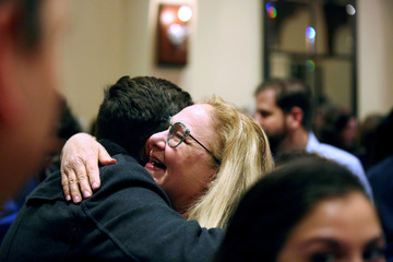 Supporters of democratic candidate Kyrsten Sinema hug after the Senator-elect spoke to the crowd after officially winning the U.S. Senate race, in Scottsdale