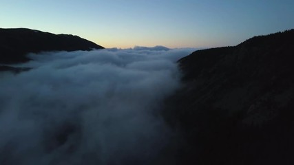 Fototapete - 4k aerial drone footage.  Colorado Rocky Mountains covered in fog at sunset