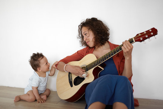 Picture of cute barefooted one year old infant boy sitting on floor with his positive young mom who is playing guitar, singing his favorite lullaby. People, music, children and entertainment