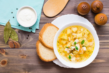 Fresh chicken broth soup with potatoes and herbs in a white bowl on a wooden table. Top view