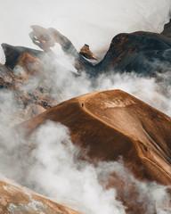 Hiker on volcanic landscape steam fog mountains