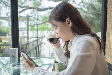 portrait background young business woman drinking coffee and using mobile phone in restaurant with glass are backdrop
