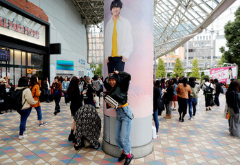 A girl poses in front of a wall photo of a member of South Korean boy band BTS outside Tokyo Dome where the band's concert will be held in Tokyo