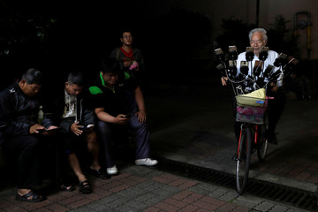"""Taiwanese Chen San-yuan, 70, known as """"Pokemon grandpa"""", rides his bicycle as he plays the mobile game """"Pokemon Go"""" by Nintendo, near his home with 15 mobile phones, in New Taipei City, Taiwan"""