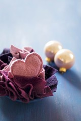 Felt love-heart and pieces of felt in bowl next to Christmas-tree baubles