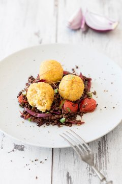 Quinoa and lupine balls on a bed of balsamic lentils