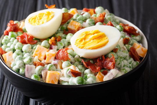 English cuisine pea salad with boiled eggs, onions, bacon and cheddar cheese with sauce close-up in a bowl. horizontal