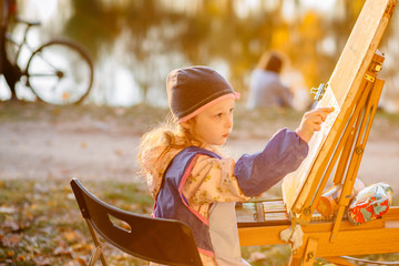 Blond little girl drawing on the easel outdoor in summer park. Child paints in sunset. Open air activity for school age children concept.